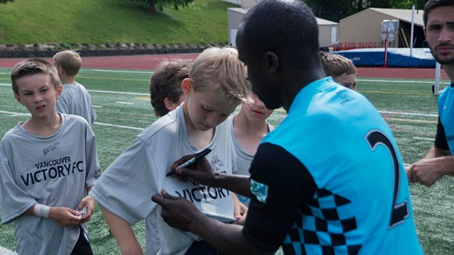 Alex Nimo signing autographs after the match