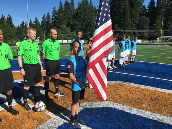 Kysho Barnhill holding the American flag for the Pledge of Allegiance.